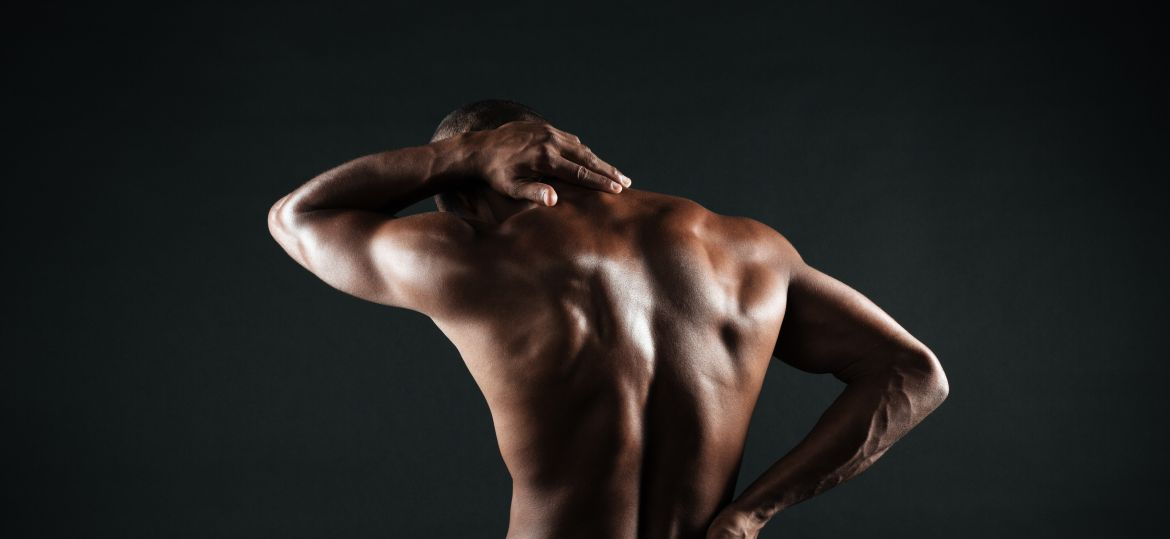 Back view of young african sports man feeling pain in his back