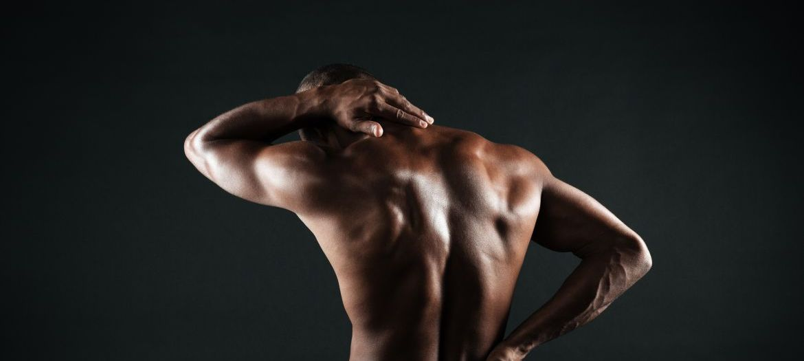 Back view of young african sports man feeling pain in his back, isolated on black background